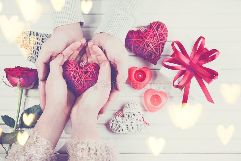 De dag van de valentijnskaart `s Jonge paarhanden die giftdoos over witte houten achtergrond houden royalty-vrije stock fotografie