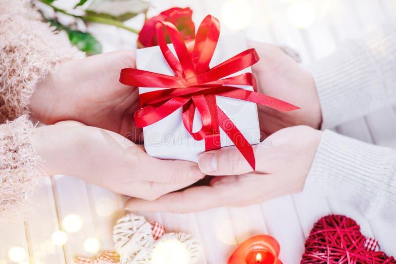 De dag van de valentijnskaart `s Jonge paarhanden die giftdoos over witte houten achtergrond houden Het concept van de liefde royalty-vrije stock afbeeldingen