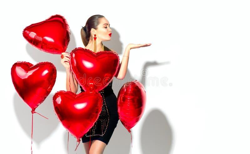 De dag van de valentijnskaart `s Schoonheidsmeisje met rode hart gevormde luchtballons die pret hebben royalty-vrije stock afbeelding