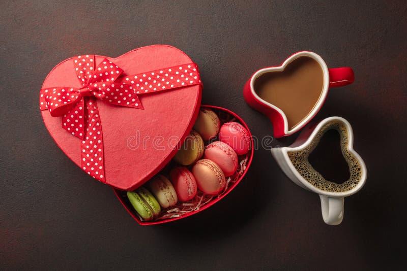 De Dag van Valentine met giften, een hart-vormige doos, koppen van koffie, hart-vormige koekjes, makarons en een bord Hoogste Men royalty-vrije stock afbeeldingen
