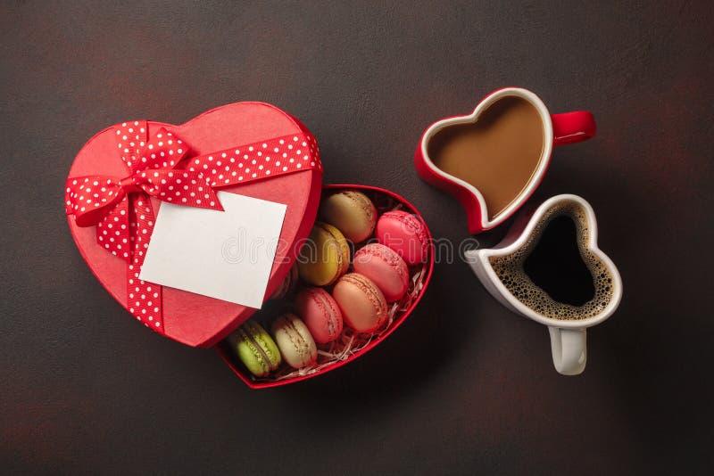 De Dag van Valentine met giften, een hart-vormige doos, koppen van koffie, hart-vormige koekjes, makarons en een bord Hoogste Men royalty-vrije stock afbeelding