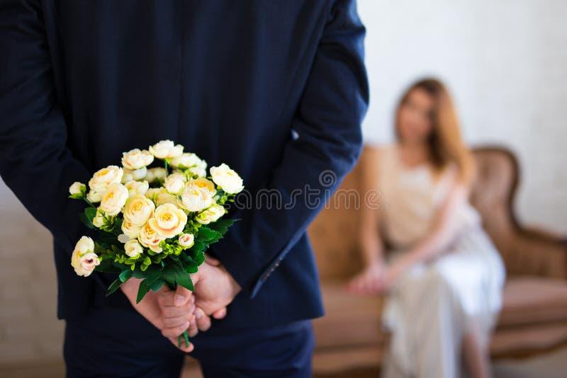 De dag van Valentine ` s of verjaardagsconcept - mens het verbergen bloemenbehi royalty-vrije stock fotografie
