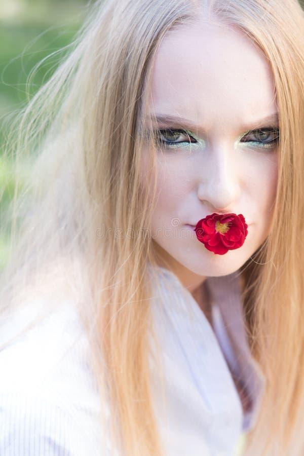 De dag van vrouwen, 8 maart, de lenteconcept Vrouw met rode bloem in mond, 8 maart Mannequin met lang blond haar stock afbeeldingen