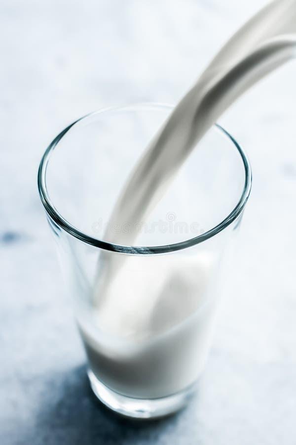 De Dag van de wereldmelk, die in glas op marmeren lijst gieten stock afbeeldingen