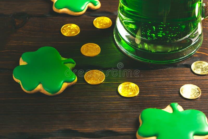 De dagachtergrond van Patrick ` s met een Glas van groene bier en klaverpeperkoek met gouden muntstukken op houten stock afbeeldingen