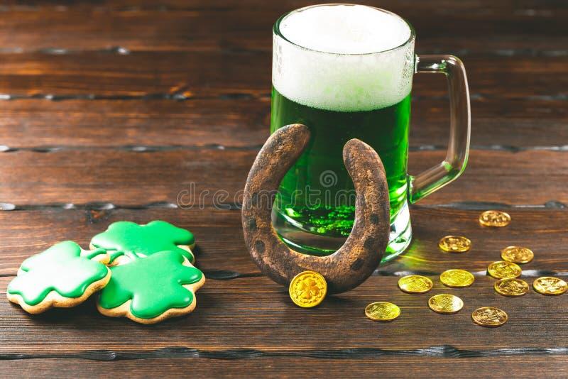 De dagachtergrond van Patrick ` s met een Glas van groene bier en klaverpeperkoek met gouden muntstukken op houten stock foto's