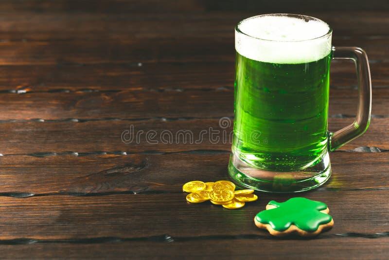 De dagachtergrond van Patrick ` s met een Glas van groene bier en klaverpeperkoek met gouden muntstukken op houten stock foto