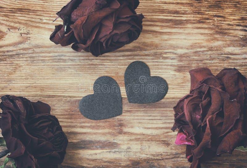 De dagachtergrond van Valentine, donkere droge rozen en zwart hart royalty-vrije stock fotografie