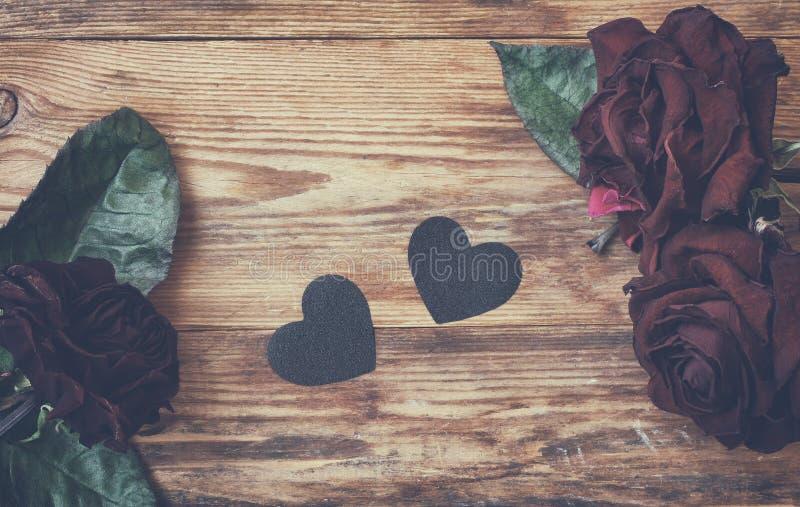 De dagachtergrond van Valentine, donkere droge rozen en zwart hart stock foto