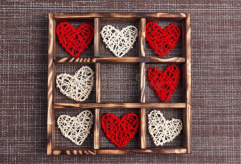 De dagachtergrond van Valentine met harten in het houten vakje op jute en celexemplaarruimte royalty-vrije stock afbeelding