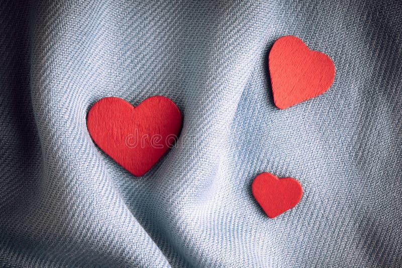 De dagachtergrond van Valentine. Rode harten op grijze vouwendoek royalty-vrije stock fotografie