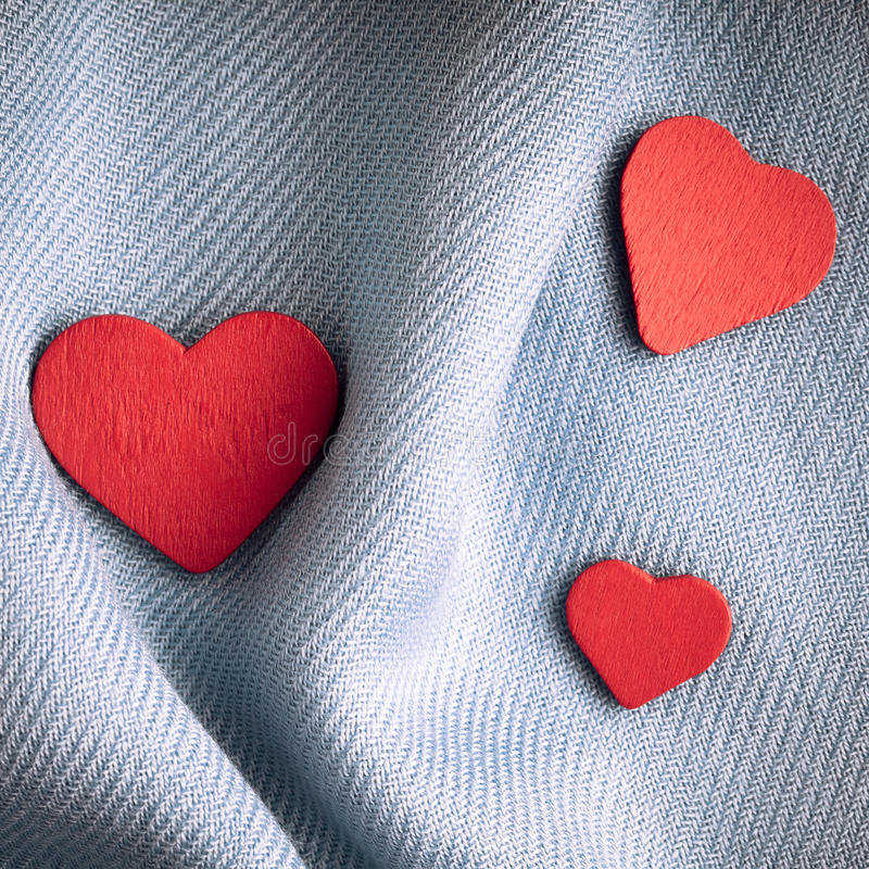 De dagachtergrond van Valentine. Rode harten op grijze vouwendoek stock afbeelding