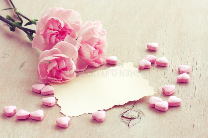 De Dagachtergrond van Valentine ` s, drie roze anjers, leeg document B royalty-vrije stock afbeeldingen