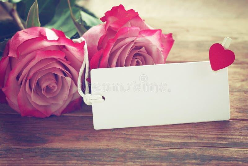 De dagachtergrond van Valentine, twee roze rozen, wit leeg etiket stock afbeeldingen