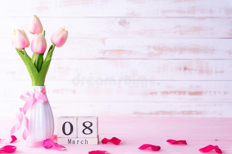 De dagconcept van internationale vrouwen Roze tulpen en rood hart met 8 Maart tekst op houten scheurkalender op witte houten acht stock foto