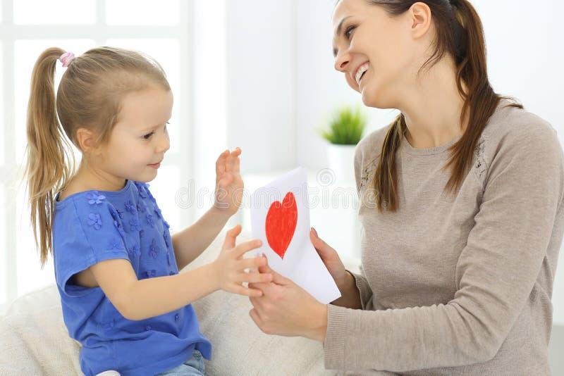 De dagconcept van de moeder ` s De kinddochter wenst mamma geluk en geeft haar prentbriefkaar met rode hartvorm Gelukkige Mum en  stock foto's