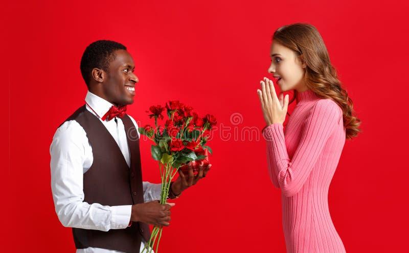 De dagconcept van de valentijnskaart ` s gelukkig jong paar met hart, bloemen, gift op rood stock foto