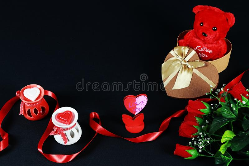 De dagconcept van de valentijnskaart ` s De teddybeer in hart vormde giftdoos met kaars en rode rozen op zwarte achtergrond royalty-vrije stock foto