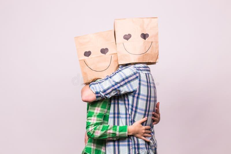 De dagconcept van Valentine ` s - Jong liefdepaar met zakken over hoofden op witte achtergrond stock foto's