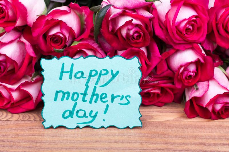 De dagkaart en rozen van de gelukkige moeder stock foto's