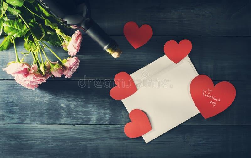 De Dagkaart van Valentine ` s met een boeket van rozen, een fles wijn en een postenvelop royalty-vrije stock foto