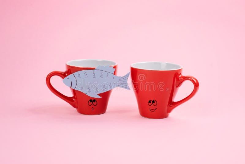 De Dagviering van April Fools ', document vissenstreek Twee het gekscheren het lachen koffiekoppen met document vissen op roze ac stock foto