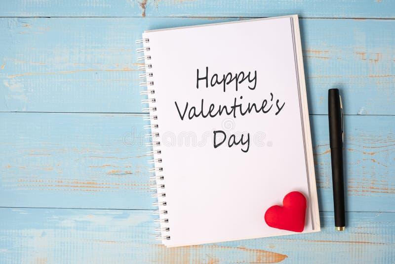 De DAGwoord van GELUKKIG VALENTINE op notitieboekje en pen met de vormdecoratie van het paar rode hart op blauwe houten lijstacht stock afbeelding