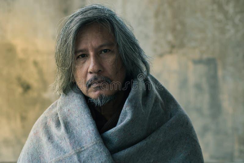 De dakloze mens met deken op de gangstraat in de stad die op vriendelijkheidsmensen wachten geeft geld of voedsel royalty-vrije stock fotografie