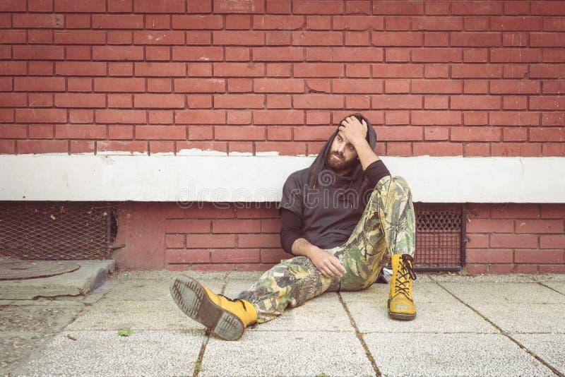 De dakloze de mensendrug en alcohol wijden zitting alleen en gedeprimeerd op de straat die tegen een rode baksteen de bouwmuur le royalty-vrije stock afbeeldingen