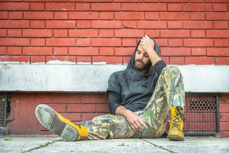 De dakloze de mensendrug en alcohol wijden zitting alleen en gedeprimeerd op de straat stock fotografie