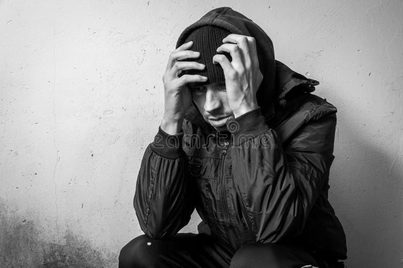 De dakloze van de mensendrug en alcohol verslaafdenzitting alleen en gedeprimeerd op de straat in de winter kleedt het voelen van stock afbeeldingen