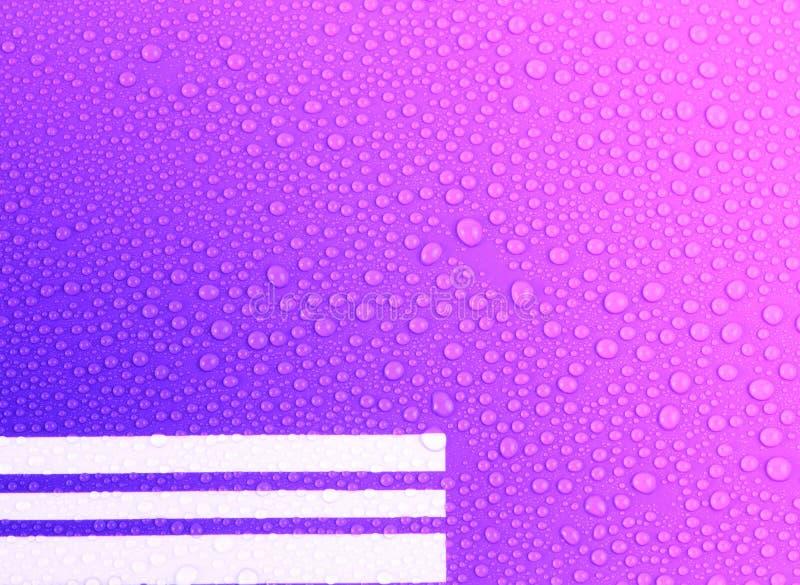 De dalingen van het water op blauwe en roze achtergrond stock fotografie