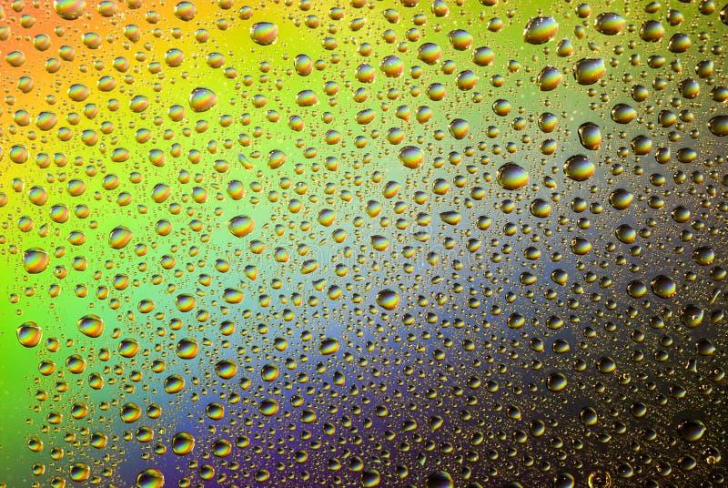 De dalingen van het water op kleurrijke achtergrond stock fotografie