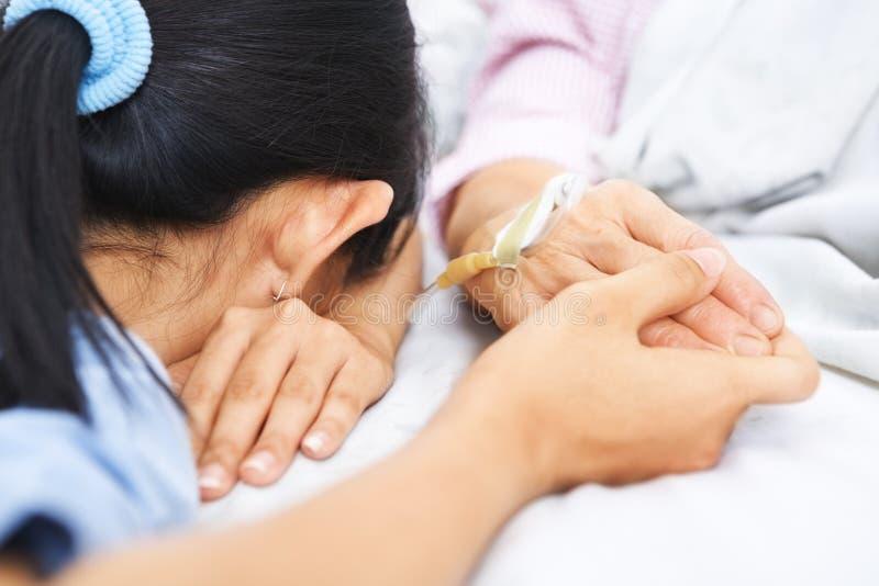 De dalings in slaap wachten van de dochter haar zieke moeder royalty-vrije stock afbeeldingen