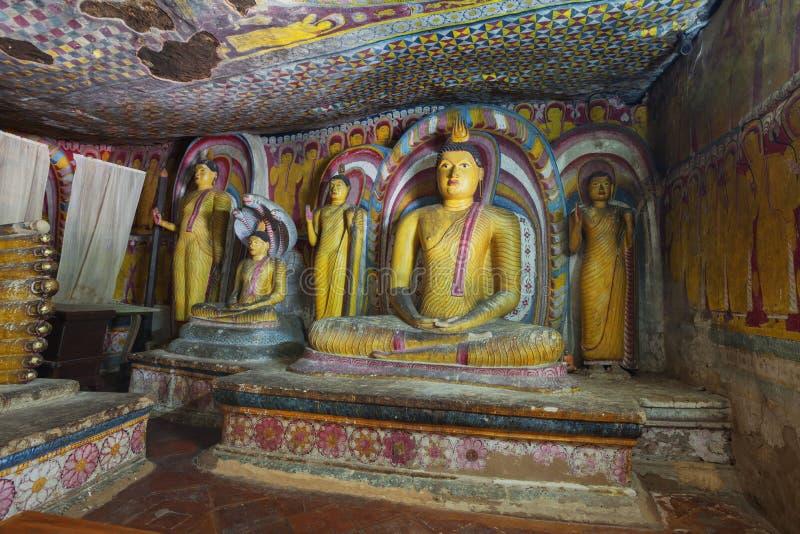 In de Dambulla-holtempel Verscheidene oude standbeelden van Boedha stock afbeelding