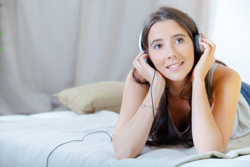 De dame die aan hoofdtelefoons luisteren propped op ellebogen stock fotografie