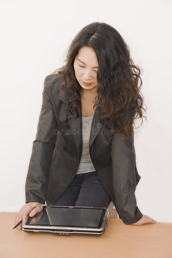 De dame die van het bureau het computerscherm bekijkt royalty-vrije stock afbeelding