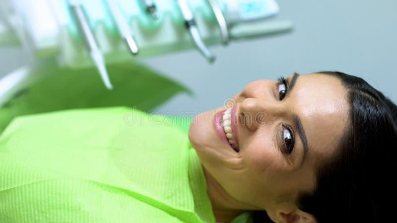 De dame kijkt aan camera met sneeuwwitte glimlach, tevredenheid met behandeling van tanden royalty-vrije stock afbeelding