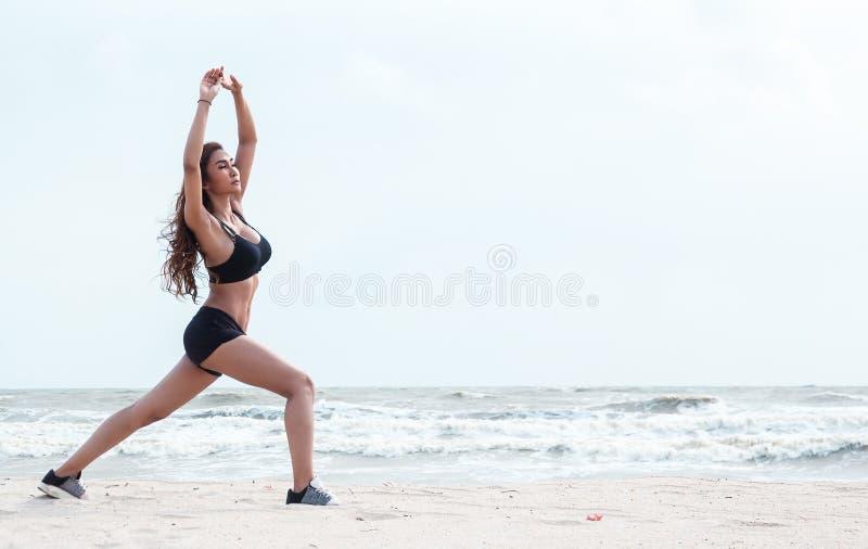 De dame met sportwear bevindt zich bij de linkerkant van achtergrond, gezette linkerbeenkant bij de rug van juist been en heft om stock afbeeldingen