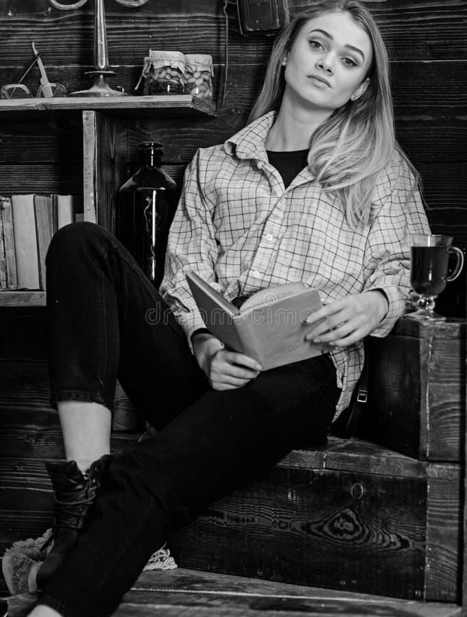 De dame op dromerig gezicht in plaidkleren kijkt toevallig Studente het ontspannen met boek en glas overwogen wijn Ontspanning stock foto's