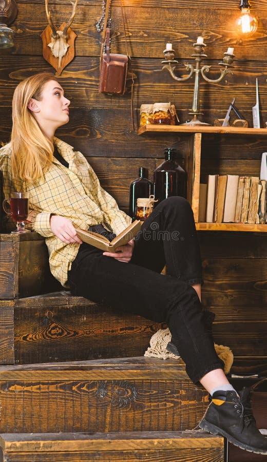 De dame op kalm gezicht in plaidkleren kijkt toevallig Hand met polshorloge in een zak Studente het ontspannen met boek en glas v stock afbeeldingen