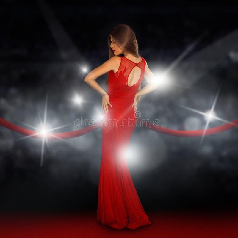 De dame op rood tapijt stelt in paparazziflitsen royalty-vrije stock fotografie