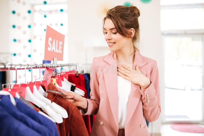 De dame in roze jasje die zich dichtbij verkoopkleren bevinden rekt gelukkig het kijken op prijs in klerenopslag royalty-vrije stock fotografie