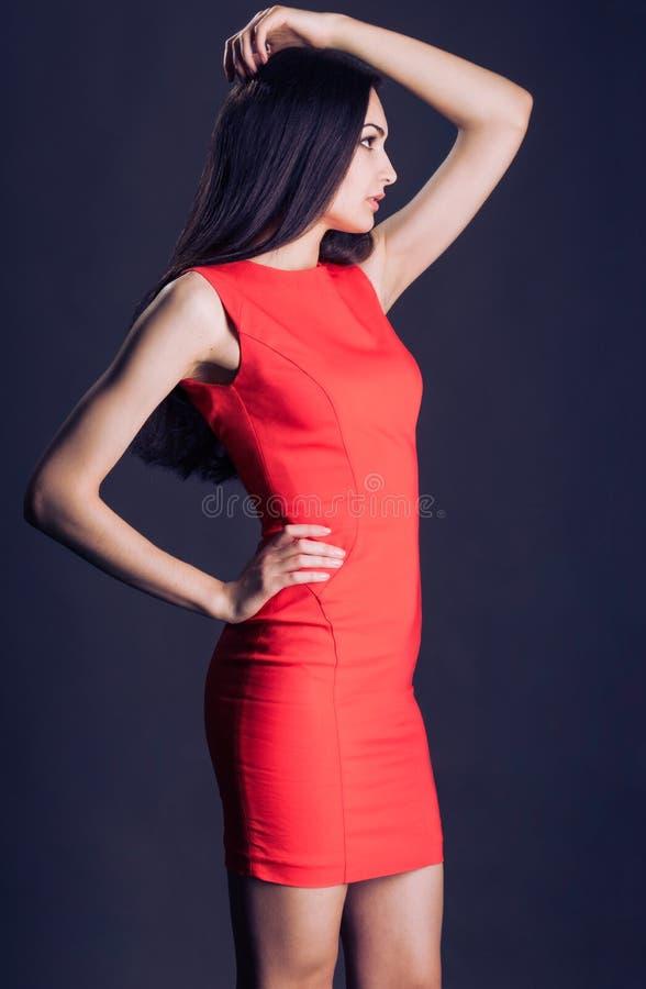 De dame van Yong met een mooi lichaam, in een profiel, goede vorm, helling en het dragen van rode kleding royalty-vrije stock afbeelding
