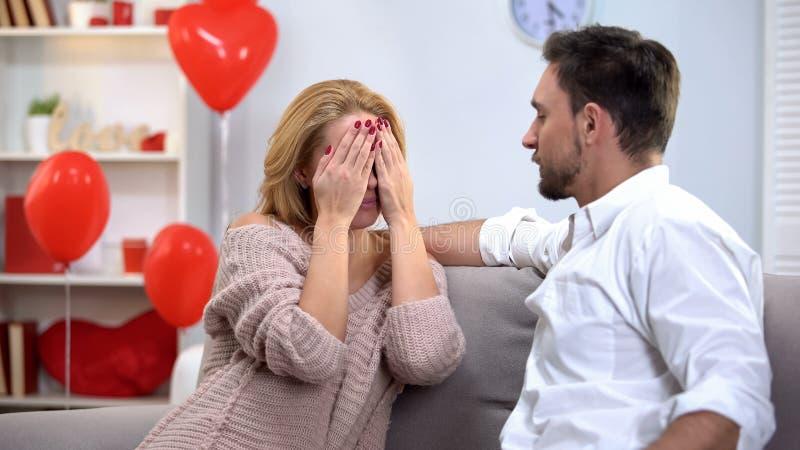 De damezitting met ogen sloot, mens die romantische verrassing op Valentijnskaartendag voorbereiden stock fotografie