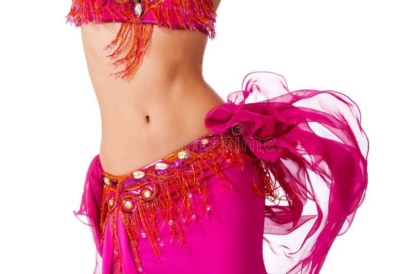 De danser van de buik in een heet roze kostuum die haar heupen schudden royalty-vrije stock afbeeldingen