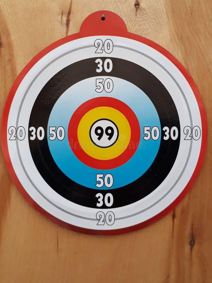 De dardos el juego es golpear dígitos brillantes redondos en una puerta de madera fotos de archivo libres de regalías