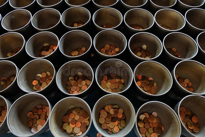 De de aalmoeskom van de monnik met zette de muntstukken door donors stock afbeeldingen