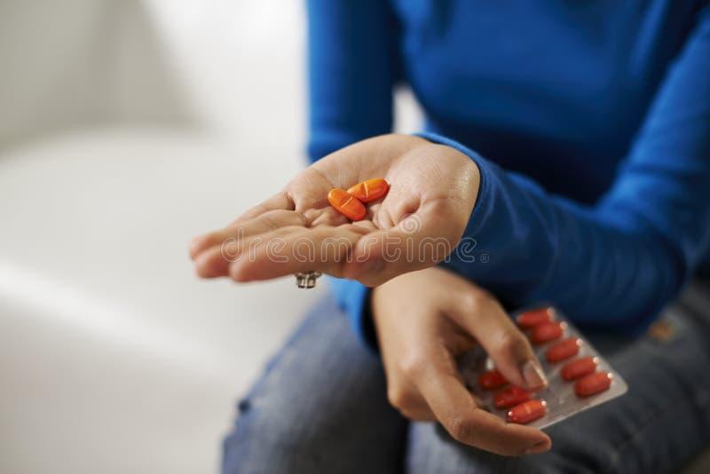 De de Aziatische pillen en geneeskunde van de vrouwenholding ter beschikking royalty-vrije stock foto