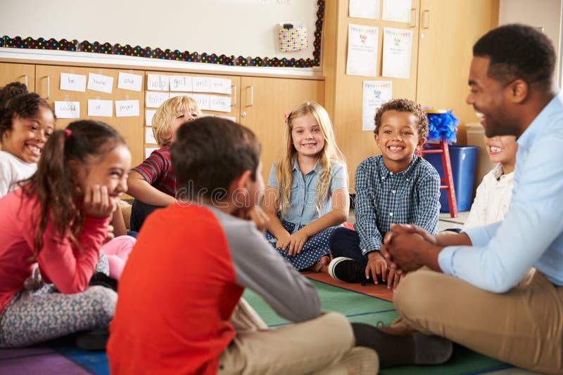 De de basisschooljonge geitjes en leraar zitten dwars legged op vloer stock fotografie